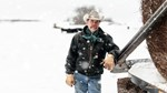 rancher in snow storm feeding cows hay